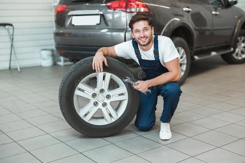 Young handsome mechanic in uniform working in car service department fixing flat tire looks pleased.  royalty free stock photo