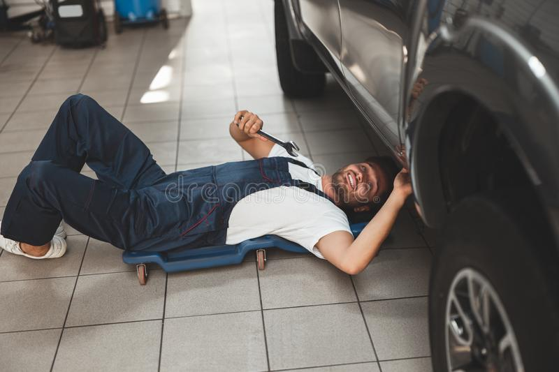 Young handsome mechanic in uniform working in car service department fixing vehicle chassis with help of spanner.  royalty free stock images