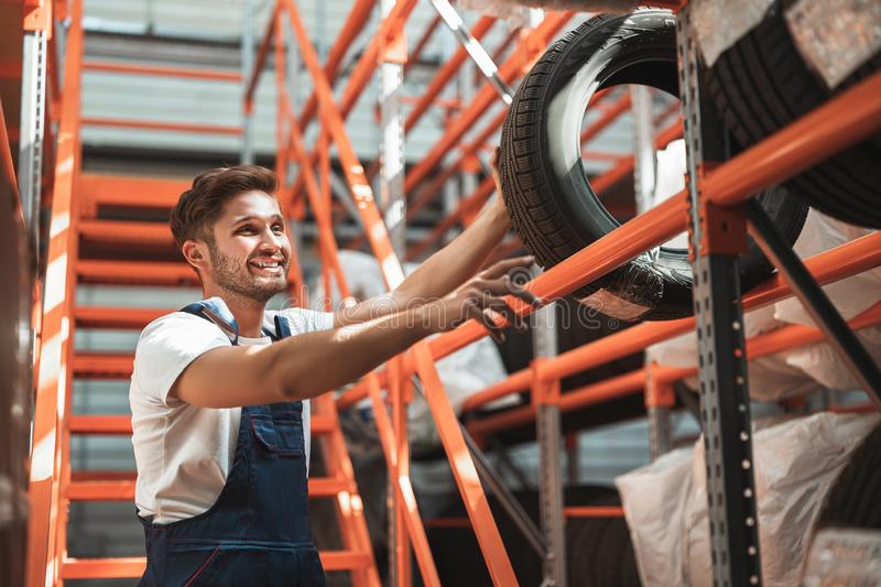 Young handsome mechanic in uniform working in car service department putting tyres for storage.  stock images