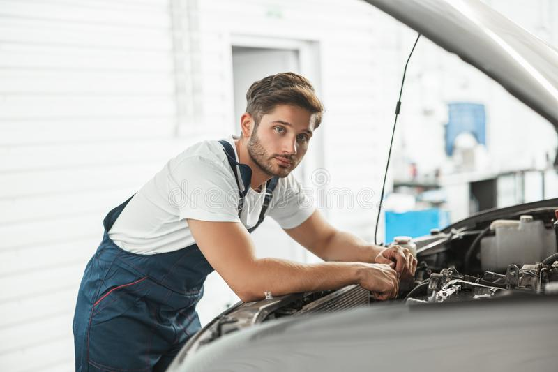 Young handsome mechanic wearing uniform fixing motor in car bonnet working in service department.  royalty free stock photos