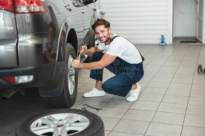 Young handsome mechanic wearing uniform working in car service department fixing flat tire looks happy.  stock image