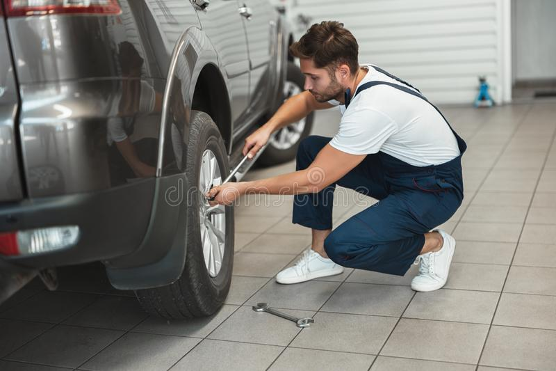 Young handsome mechanic wearing uniform working in car service department fixing flat tire with spanner.  stock image