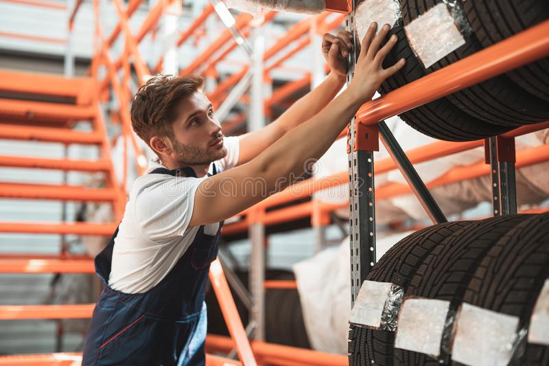 Young handsome mechanic wearing uniform working in car service department putting tyres for storage.  royalty free stock photo