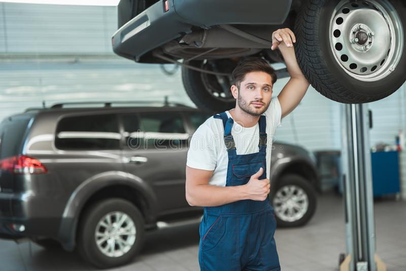 Young handsome mechanic working in car service department feeling happy showing like sign.  stock images