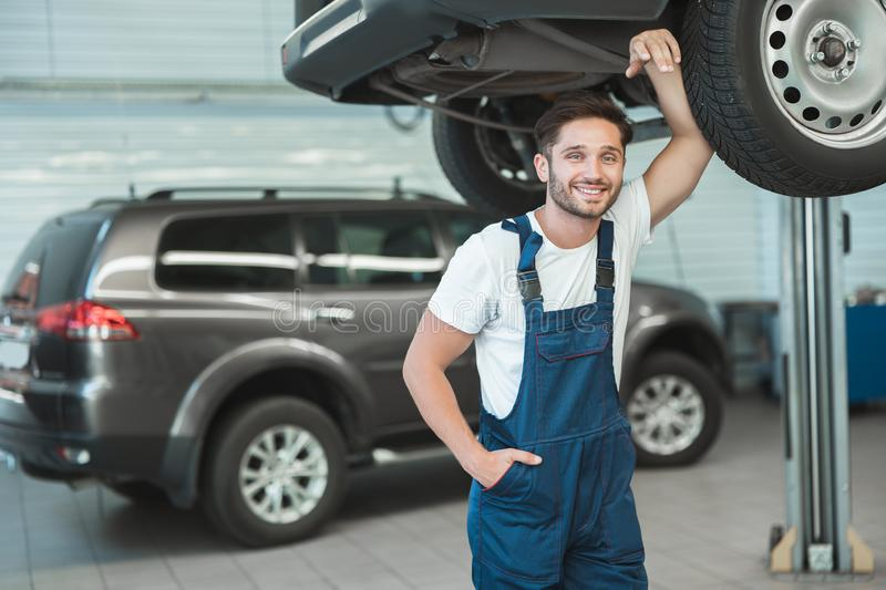 Young handsome mechanic working in car service department feeling happy.  royalty free stock photos