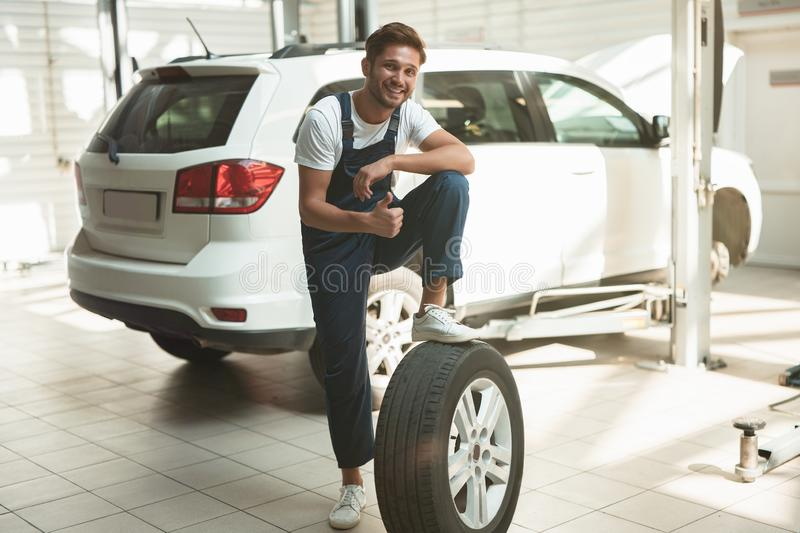 Young handsome mechanic working in car service department fixing flat tire looks playful.  stock photography