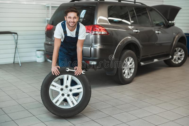 Young handsome mechanic working in car service department fixing flat tire looks pleased.  royalty free stock photography