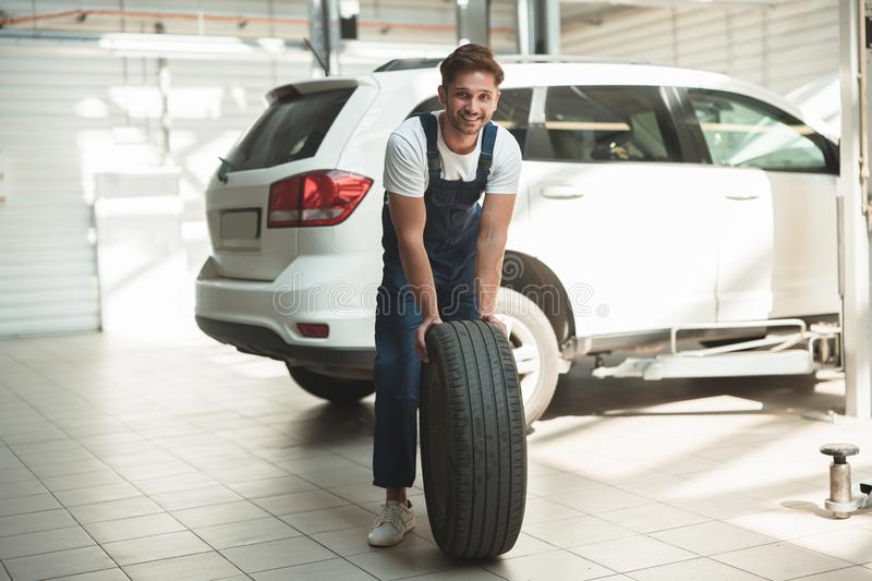 Young handsome mechanic working in car service department fixing flat tire.  royalty free stock image
