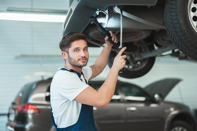 Young handsome mechanic working in car service department fixing the problem in vehicle chassis.  royalty free stock photography