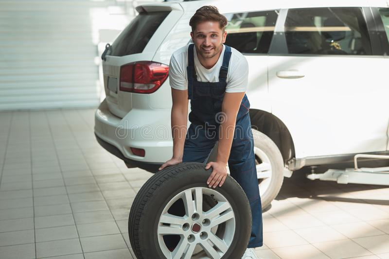 Young handsome mechanic working in car service department fixing tire.  royalty free stock image
