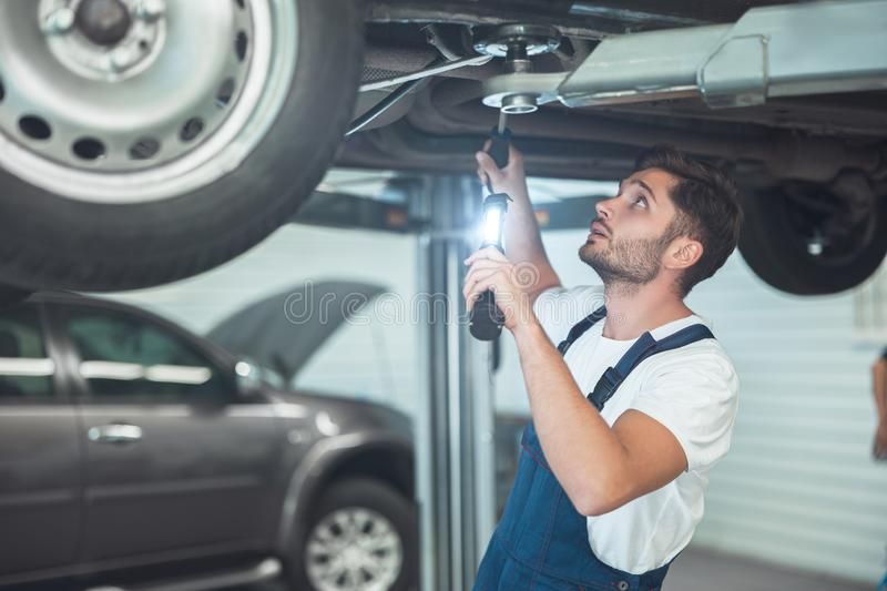 Young handsome mechanic working in car service department fixing vehicle chassis.  royalty free stock image