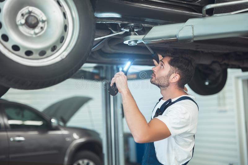 Young handsome mechanic working in car service department scanning the problem in vehicle chassis.  stock photo