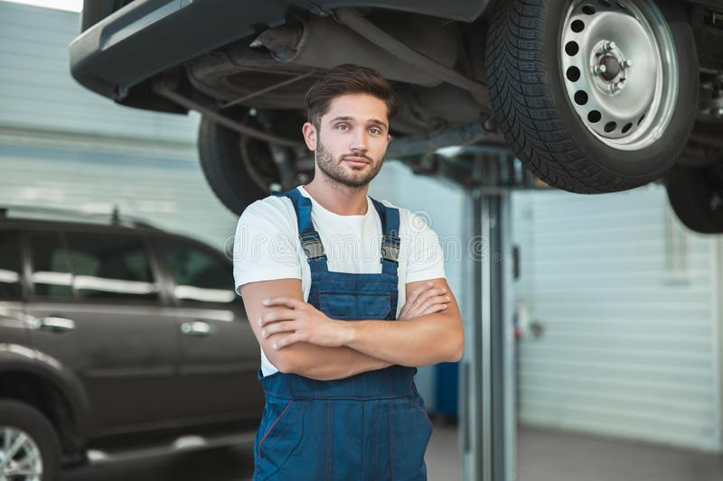 Young handsome mechanic working in car service department.  stock images