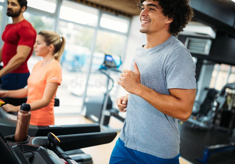Young handsome man doing cardio training in gym royalty free stock photography