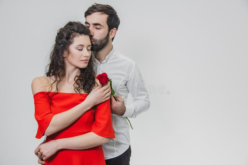 A young, handsome man gently covers his beautiful wife. During this time, one red rose. The girl is dressed in a red stock photography