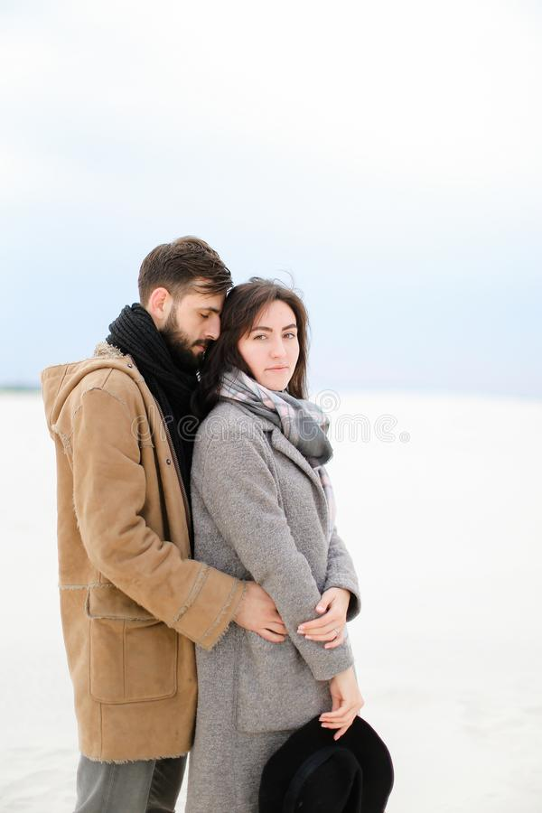 Young man hugging pretty woman wearing grey coat and scarf in white winter background. Young handsome men hugging women wearing grey coat and scarf in white royalty free stock photos