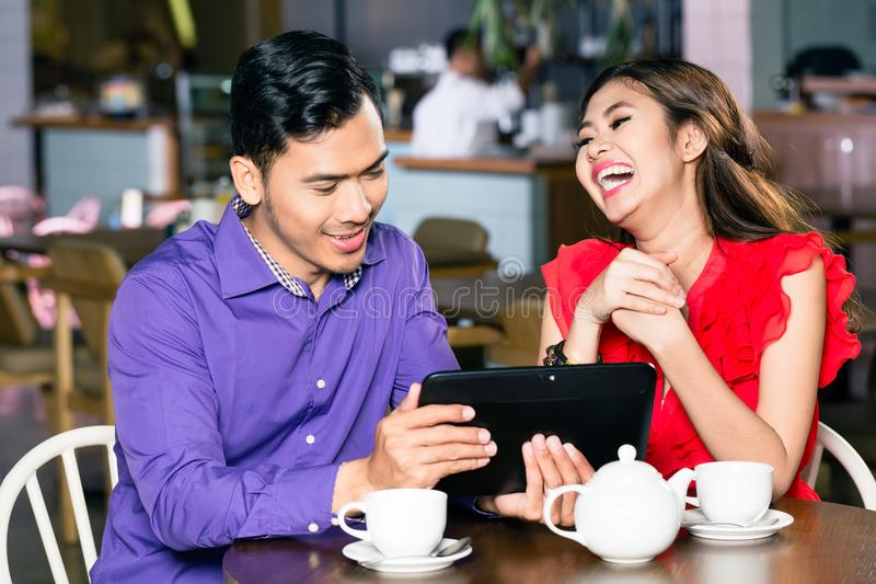 Young man watching a funny video on tablet next to his girlfriend royalty free stock image
