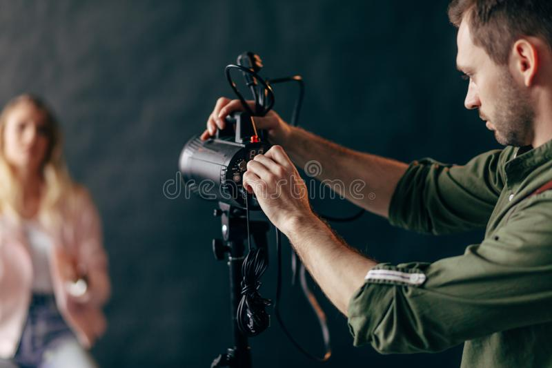 Young handsome man working with a professional studio strobe photo flash light. royalty free stock photos