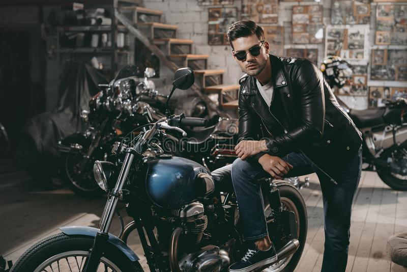 Young handsome motorcyclist in black leather jacket with classic motorbikes. In workshop royalty free stock photography