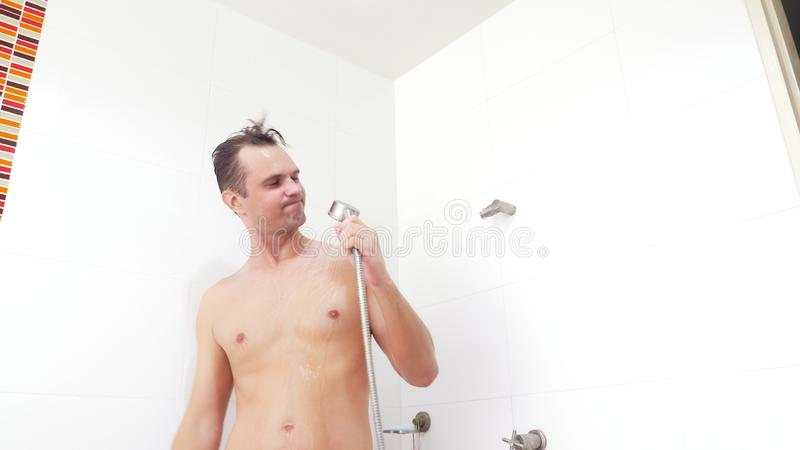 Young handsome muscular man takes a shower. the guy washes, sings and dances in the shower. stock photography