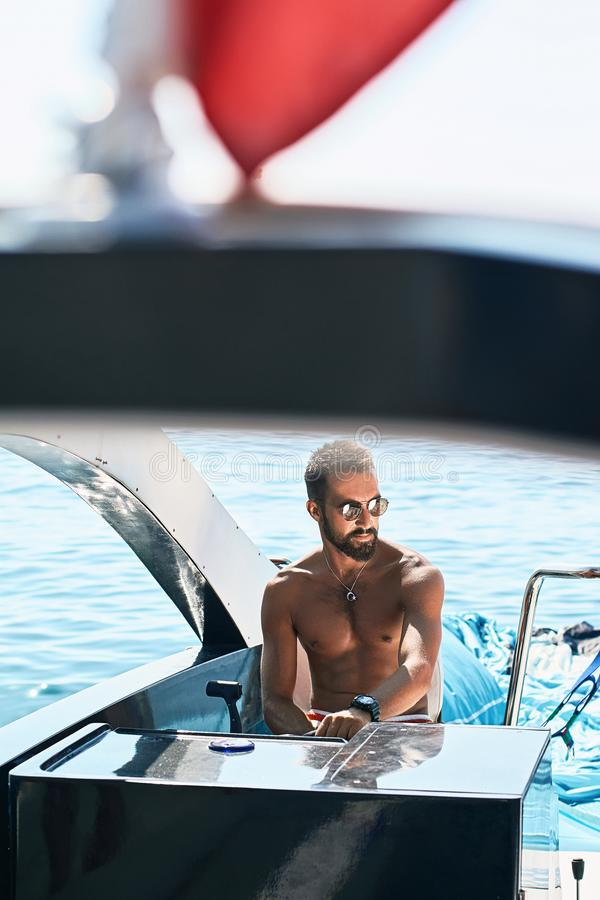 Tanned young handsome bearded muslim captain or skipper steering at the helm and control panel of a yacht under the red. Young handsome muslim captain on a stock photos