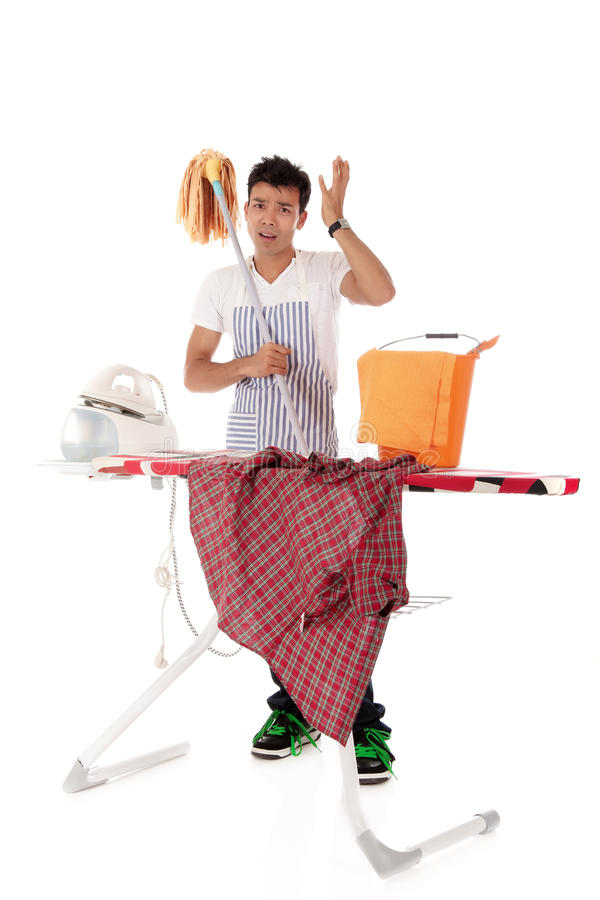 Young handsome Nepalese man, ironing, cleaning stock photography