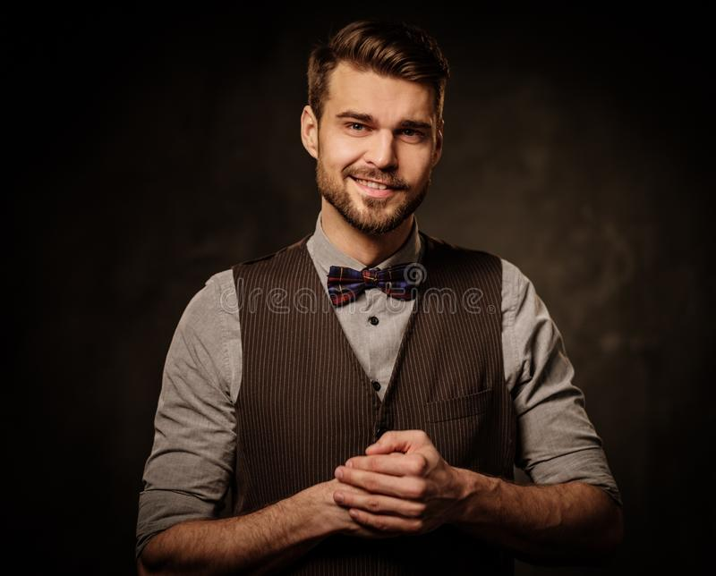 Young handsome old-fashioned man with beard posing on dark background. stock photos