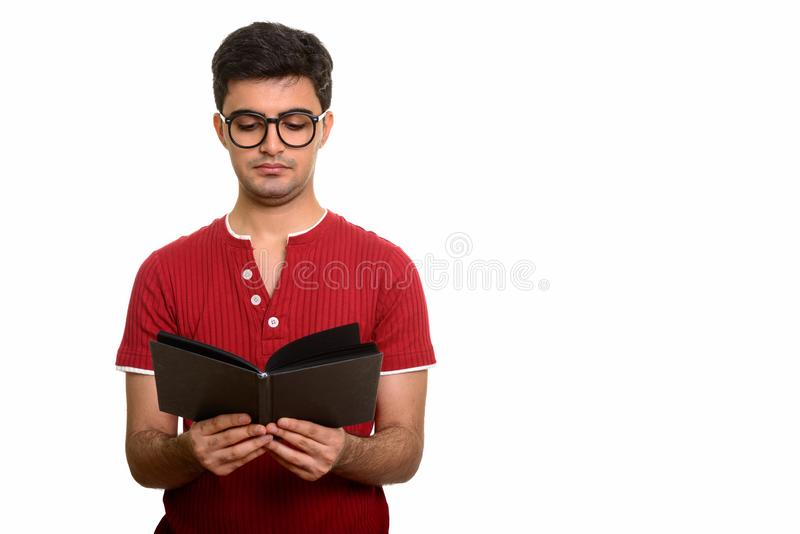 Young handsome Persian man reading book against white background stock images