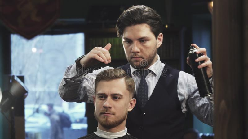 Professional barber using hairspray styling hair of a young man royalty free stock photo