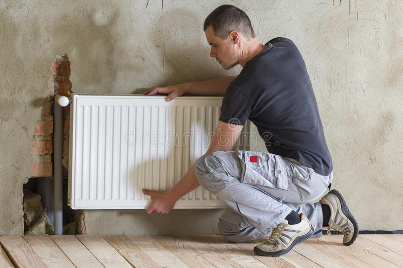 Young handsome professional plumber worker installing heating ra stock photography