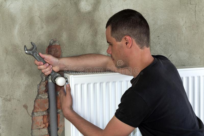 Young handsome professional plumber worker installing heating radiator on brick wall using a wrench in an empty room of a newly bu. Ilt apartment or house stock photo