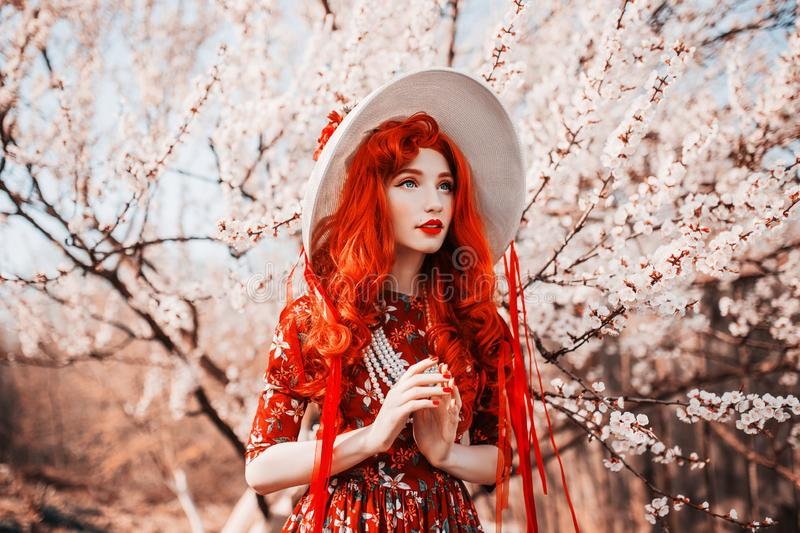 Young handsome redhead girl in spring flower garden. Woman in vintage hat and  retro dress on nature. Beautiful spring cherry tree stock images