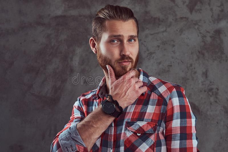 Young handsome redhead model man in a flannel shirt on a gray background. royalty free stock image
