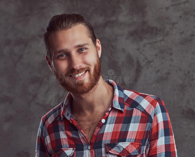 Young handsome redhead model man in a flannel shirt on a gray background. royalty free stock images