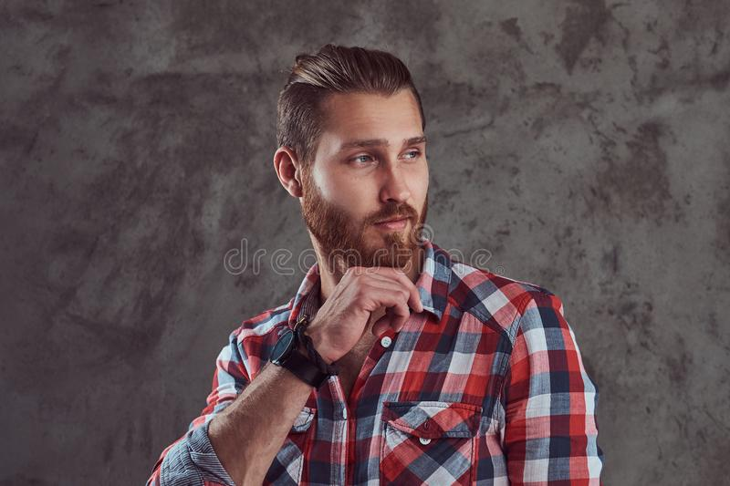 Young handsome redhead model man in a flannel shirt on a gray background. stock images