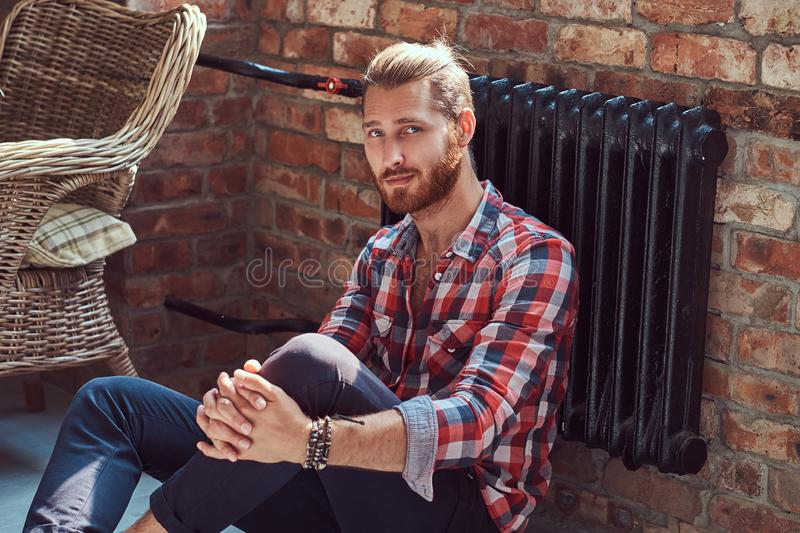 Young handsome redhead model man sits on a floor in the room with a loft interior. royalty free stock photos