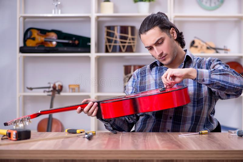 Young handsome repairman repairing guitar royalty free stock images