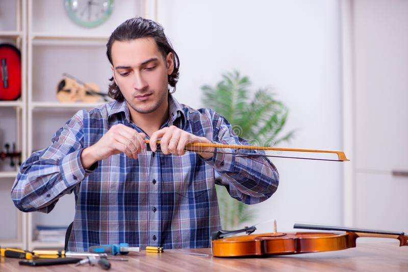 Young handsome repairman repairing violin royalty free stock image