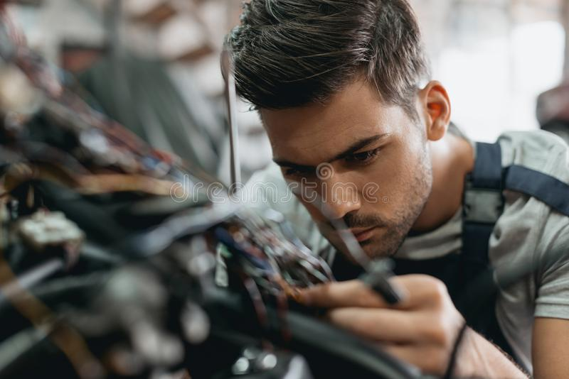 young handsome repairman working with motorcycle royalty free stock images