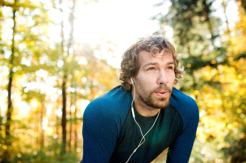 Young handsome runner with earphones outside in autumn nature. Young handsome runner with earphones in his ears, listening music, outside in sunny autumn nature royalty free stock images