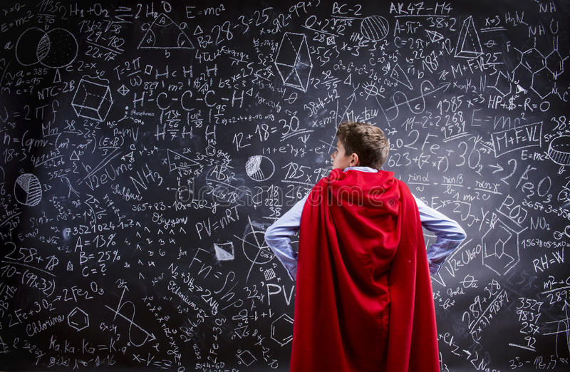 Young handsome school boy. With red cape in front of big blackboard royalty free stock image