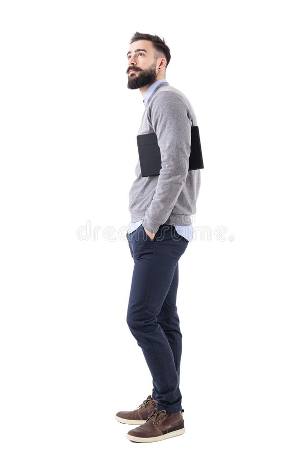 Young handsome smart casual with planner under arms looking up. Side view stock photos
