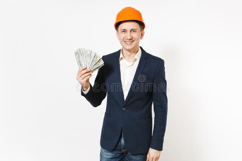 Young handsome smiling businessman in dark suit, protective construction helmet holding bundle of dollars, cash money stock photos