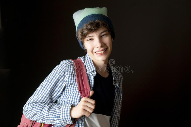 Young handsome smiling male with backpack in casual isolated on dark background f stock photos