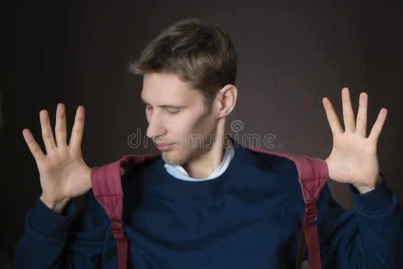 Young handsome smiling male with backpack in casual on dark background f stock image