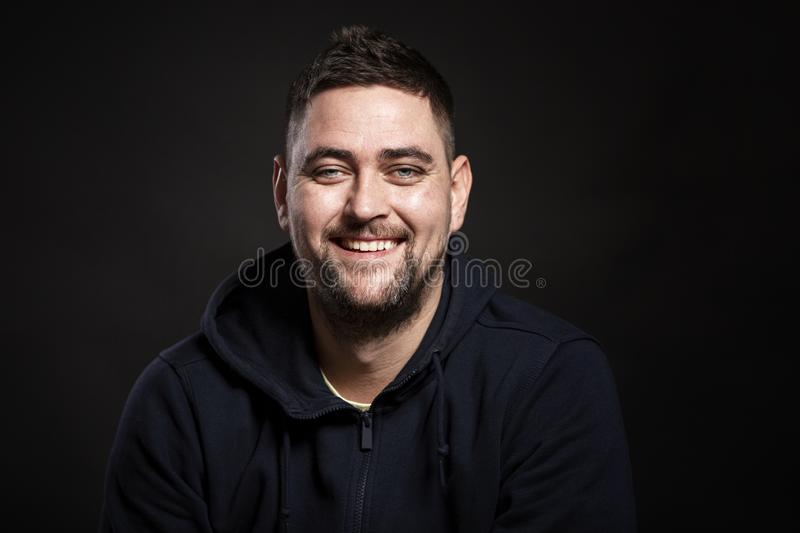 A young handsome smiling man in a blue hoodie is sitting and looking at the camera. Black background. Close-up stock photo
