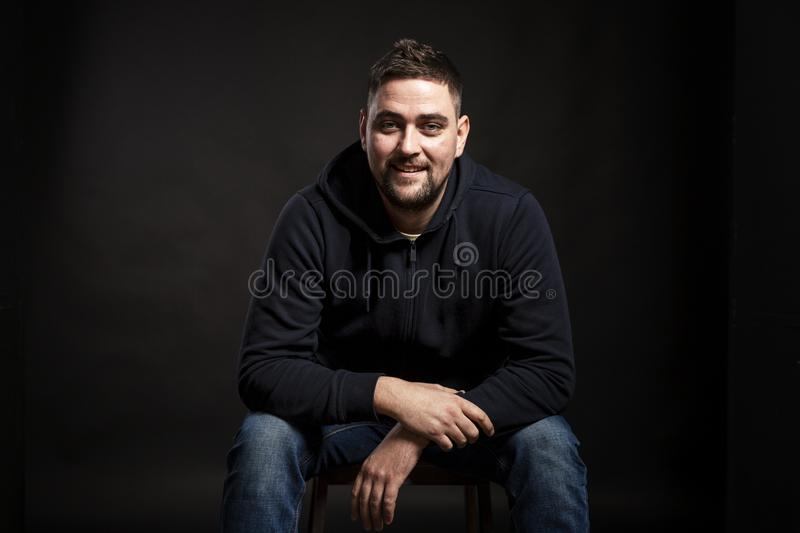 A young handsome smiling man in a blue hoodie is sitting and looking at the camera. Black background royalty free stock photography