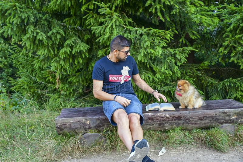 Young handsome smiling man  reading outdoor with a dog stock image