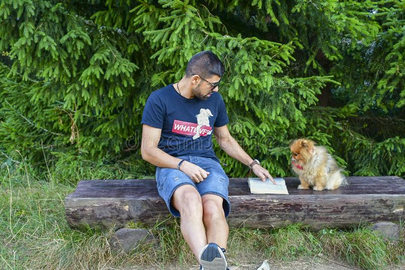 Young handsome smiling man  reading outdoor with a dog stock photos