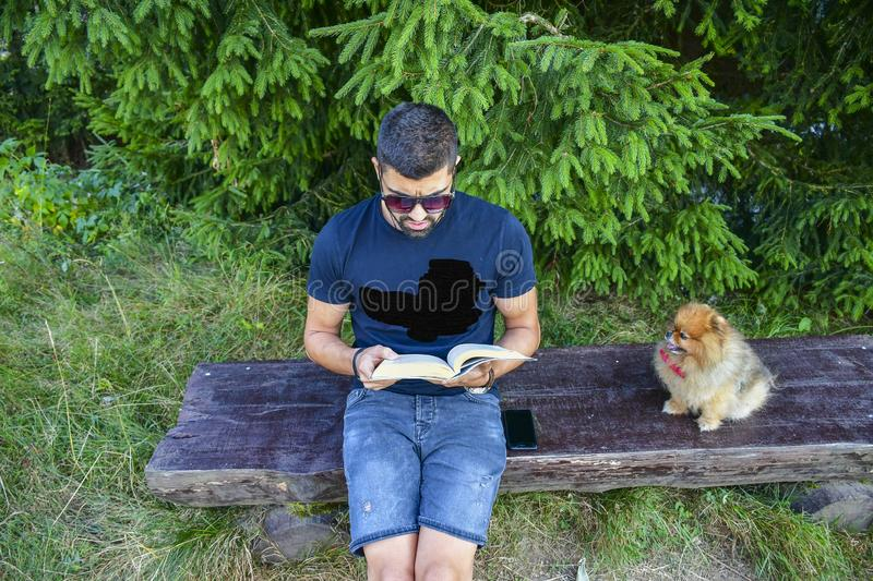 Young handsome smiling man  reading outdoor with a dog royalty free stock image